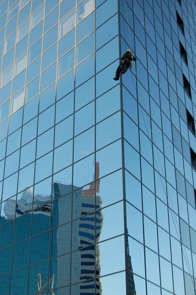 Inimene klaasist kõrghoonel ronimas