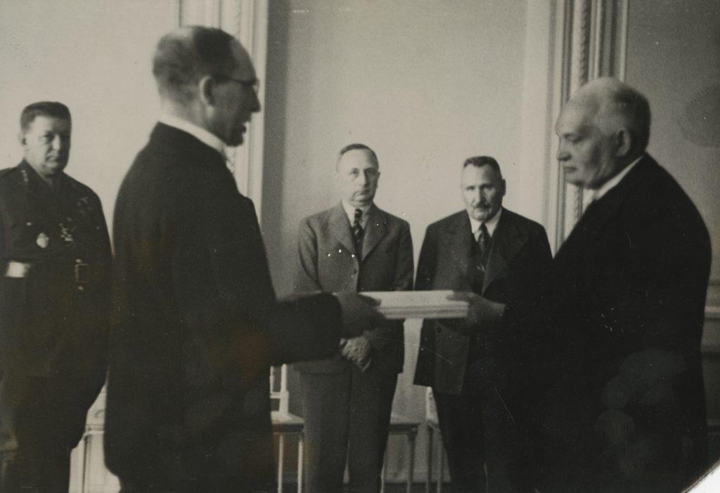 Jüri Uluots andmas Konstantin Pätsile üle Rahvuskogus 1937. aastal heaks kiidetud põhiseadust. Uue põhiseaduse alusel asus Riigikogu taas tööle, kuid demokraatia taastamist ei toimunud.